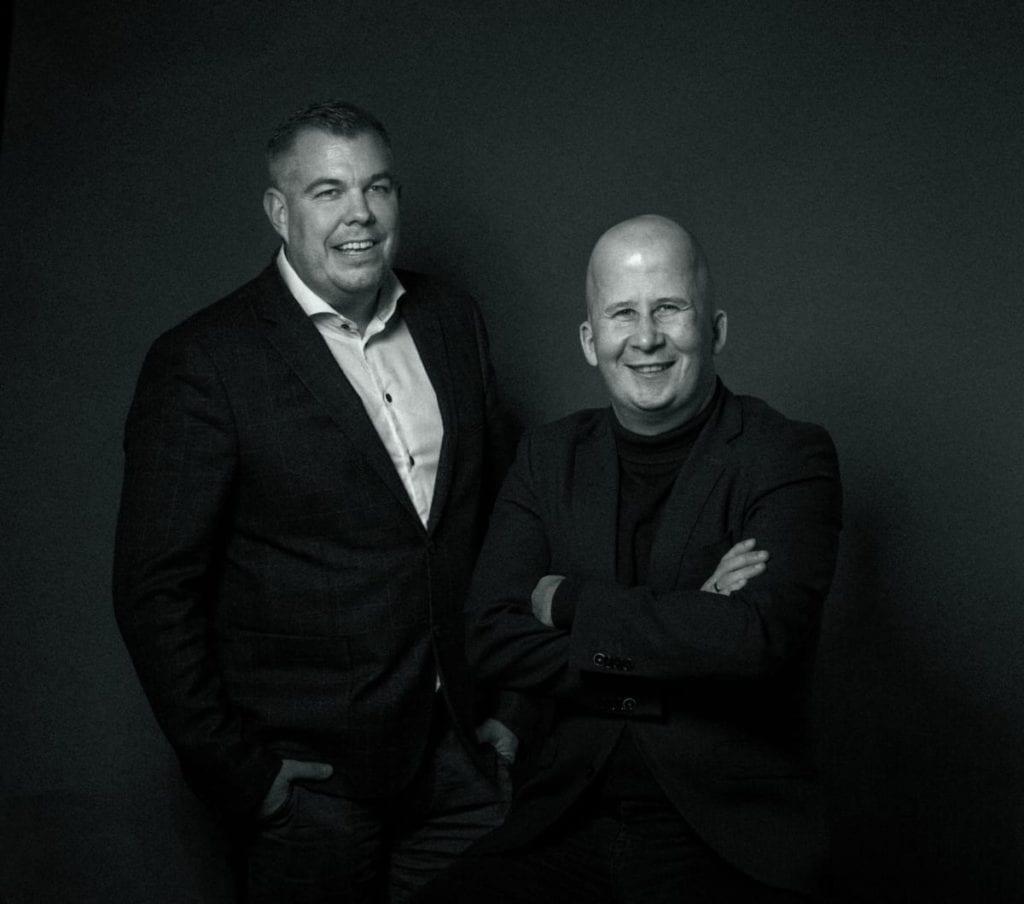To mænd der sidder ved siden af hinanden og smiler.